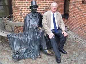 photo of Geoff Plant, seated, posing next to bronze statue